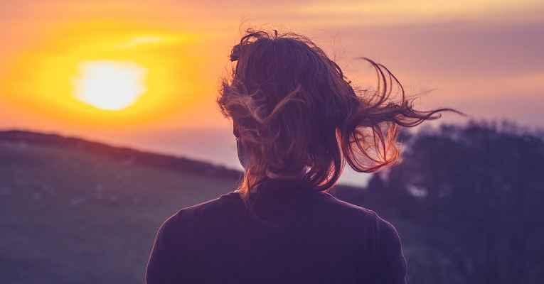 Mulher vendo o nascer do sol sozinha