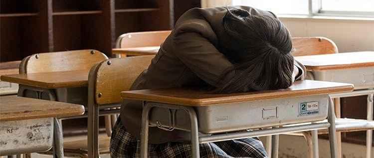 Estudante com a cabeça abaixada na carteira