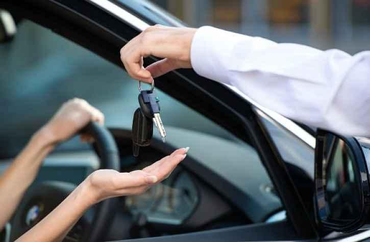 Pessoa dentro do carro recebendo chaves