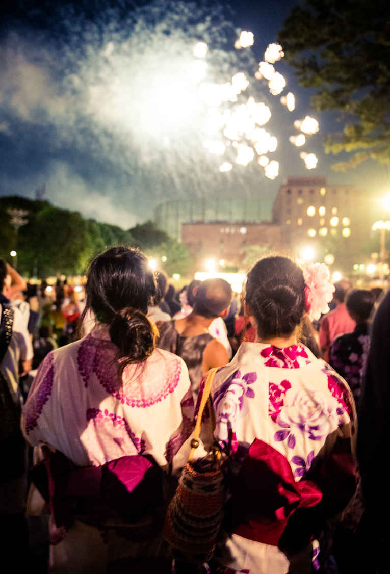 Pessoas vestindo yukata e vendo os fogos
