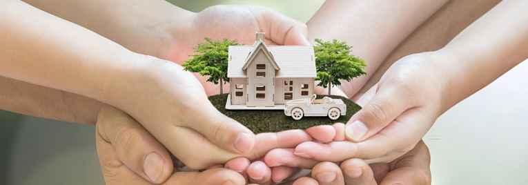 Casa em miniatura e mãos ao redor protegendo