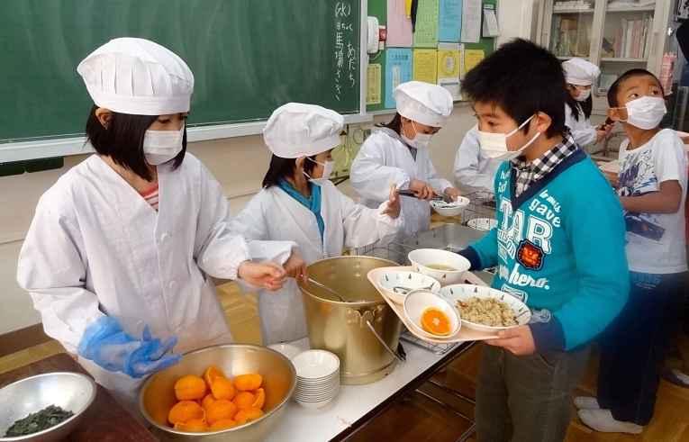 Crianças servindo merenda