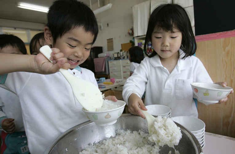 Crianças servindo arroz