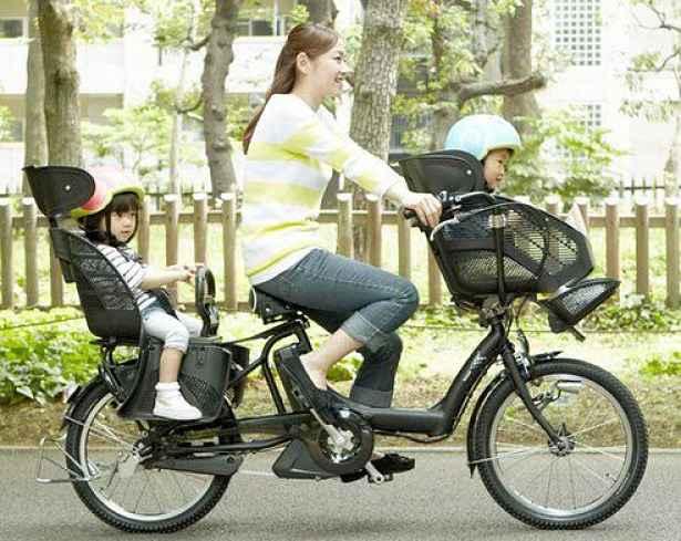 Mulher com duas crianças na bicicleta