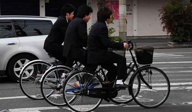 Três homens emparelhados com a bicicleta
