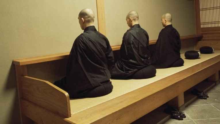 Monges meditando virados para a parede