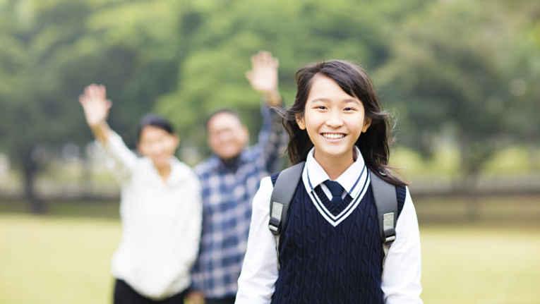 Criança indo para a escola feliz e seus pais ao fundo