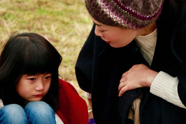 mulher e criança agachada