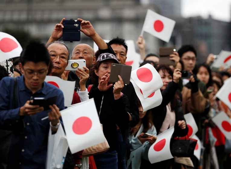 População nas ruas com bandeiras do Japão
