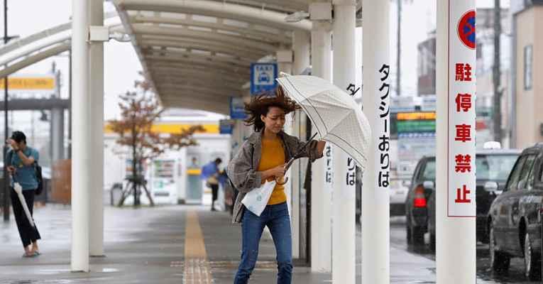 Mulher andando de guarda-chuva no meio do vento