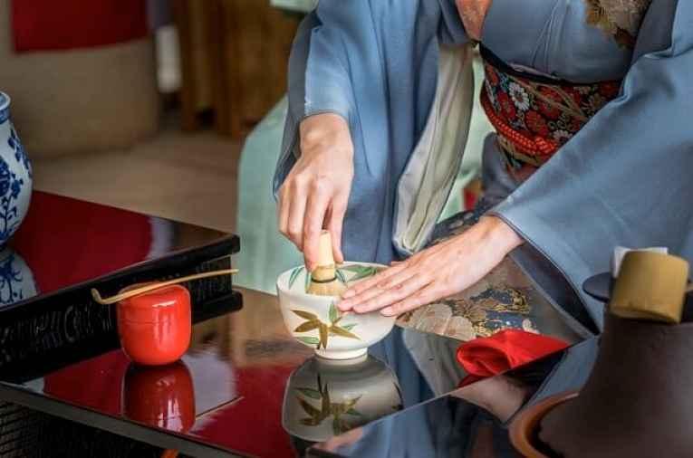 Mulher misturando matcha seco na xícara