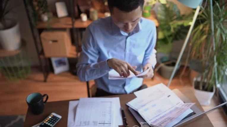 Homem na frente do notebook com contas de papel